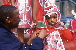 Man adjusting costume for child taking part in street carnival,