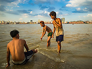 04 NOVEMBER 2015 - YANGON, MYANMAR:  Burmese men in Dala cool off in the Yangon River. Yangon is in the background. Dala is located on the southern bank of Yangon River across from downtown Yangon, Myanmar. Many Burmese live in Dala and surrounding communities and go across the river into central Yangon for work. Before World War 2, the Irrawaddy Flotilla Company had its main shipyards in Dala. That tradition lives on in the small repair businesses the work on the hundreds of small wooden boats that serve as commuter ferries for the people of Yangon. The boats are pulled up onto the riverbank in Dala and repaired by hand.   PHOTO BY JACK KURTZ