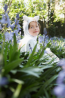 Portrait of young girl (5-6) sitting in flowers in horse costume