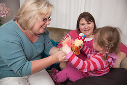 Toddler with her mum and grandmother on a sofa playing with toys