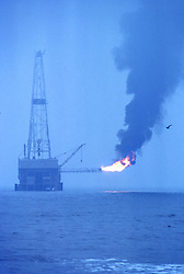 Stock photo of an offshore bay barge drilling rig flaring off waste gas in Southern Louisiana