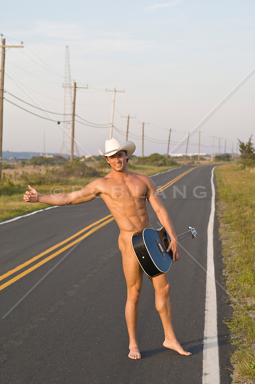 naked cowboy holding a guitar hitchhiking on an empty road