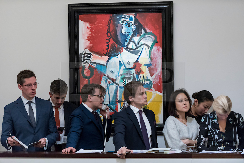 "© Licensed to London News Pictures. 01/03/2017. London, UK. Sotheby's staff, bidding on behalf of telephone clients, stand in front of ""Femme Nue Assise"" by Pablo Picasso which sold for a hammer price of GBP12m (est. GBP9.5-12.5m) at the evening sale of Impressionist and Surrealist Art at Sotheby's in New Bond Street. Photo credit : Stephen Chung/LNP"
