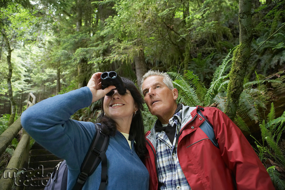 Senior man and middle-aged woman in forest woman looking through binoculars