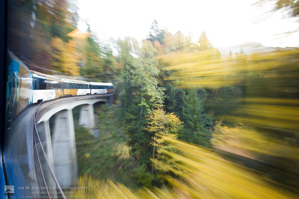 Fall color from golden leafed trees blurs the view as the Golden Pass Panoramic train travels over a bridge toward Interlaken, Switzerland