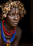 Portrait of a young Dassanech woman wearing bottle caps as headgear and beaded necklaces. Omo Valley, Ethiopia.