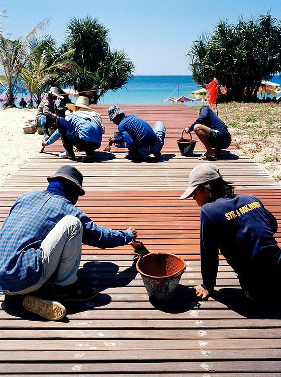 Thai workers re-paint the beach boardwalk
