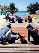 Thai workers re-paint the beach boardwalk