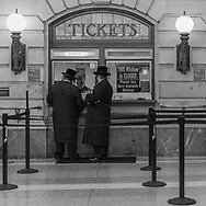 Men of the cloth buying train tickets in the Hoboken Train Station