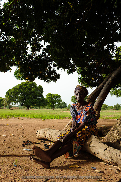 Ivona Gang-Man sitting under a tree early in the morning in the village of Lyssah in the Upper West region of Ghana. Once their eyesight begins to fail, as Ivona's is, there is often little to occupy the elderly in rural communities such as this.