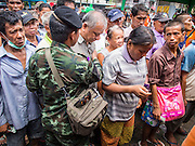 "07 AUGUST 2014 - BANGKOK, THAILAND:     People wait to get into a food distribution at Pek Leng Keng Mangkorn Khiew Shrine in Bangkok. Thousands of people lined up for food distribution at the Pek Leng Keng Mangkorn Khiew Shrine in the Khlong Toei section of Bangkok Thursday. Khlong Toei is one of the poorest sections of Bangkok. The seventh month of the Chinese Lunar calendar is called ""Ghost Month"" during which ghosts and spirits, including those of the deceased ancestors, come out from the lower realm. It is common for Chinese people to make merit during the month by burning ""hell money"" and presenting food to the ghosts. At Chinese temples in Thailand, it is also customary to give food to the poorer people in the community.  PHOTO BY JACK KURTZ"
