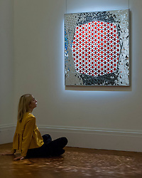 "© Licensed to London News Pictures. 13/10/2016. London, UK. A Sotheby's staff member views ""Variations on Hexagon of Octagon Mirrors, 2005"" by Monir Farmanfarmaian (est. GBP 120-150k) at the preview of Sotheby's Art of the Middle East and India exhibition, which presents artworks to be sold in New Bond Street in four sales in October. Photo credit : Stephen Chung/LNP"