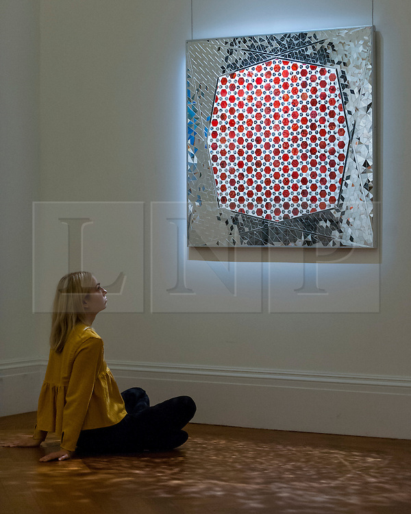 """© Licensed to London News Pictures. 13/10/2016. London, UK. A Sotheby's staff member views """"Variations on Hexagon of Octagon Mirrors, 2005"""" by Monir Farmanfarmaian (est. GBP 120-150k) at the preview of Sotheby's Art of the Middle East and India exhibition, which presents artworks to be sold in New Bond Street in four sales in October. Photo credit : Stephen Chung/LNP"""