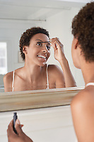 Woman applying mascara in mirror at home