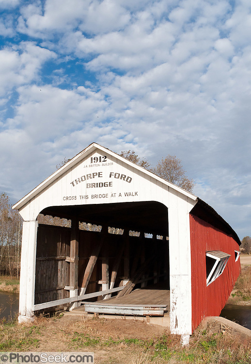 "Thorpe Ford Covered Bridge (163 feet long) was built in Burr Arch style over Big Raccoon Creek in 1912 by J.A. Britton on Catlin Road in Parke County, Indiana, USA. Red and white paint protects the wood. The traditional ""Cross this bridge at a walk"" sign required slow vehicle speed, but traffic is now diverted to an adjacent modern bridge. Puffy white clouds decorate the blue sky."