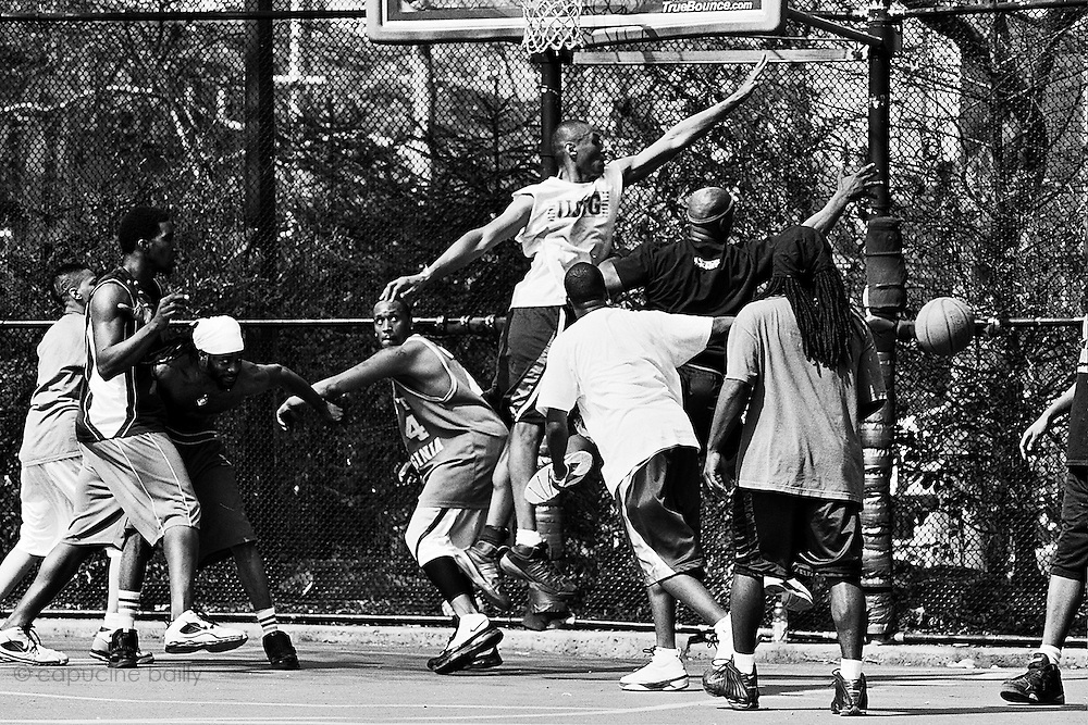 "April 19th 2008. New York, New York. United States..Located in the heart of Greenwich Village, the West 4th Street basketball Court, known as ""The Cage"", offers no seating but attracts the best players and a lot of spectators as soon as spring is around the corner..Half the size of a regular basketball court, it creates a fast, high level of play. The more people watch, the more intense the games get. « The Cage » is a free show. Amazing actions, insults and fights sometimes, create tensions among and inside the teams. The strongest impose their rules. Charisma is present..""The Cage"" is a microcosm. It's a meeting point for the African American street culture of New York. Often originally from Jamaica or other islands of the Caribbean, they hang out, talk, joke, laugh, comment the game, smoke… Whether they play or not, they're here, inside ""The Cage"". Everybody knows everybody, they all greet each other, they shake hands and hug: ""Yo, whasup man?"""