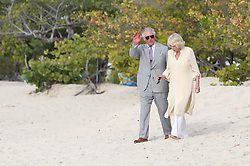 The Prince of Wales and the Duchess of Cornwall walk along Grand Anse beach during a one day visit to the Caribbean island of Grenada.
