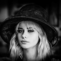 Vignetted shot of blonde female model wearing a hat