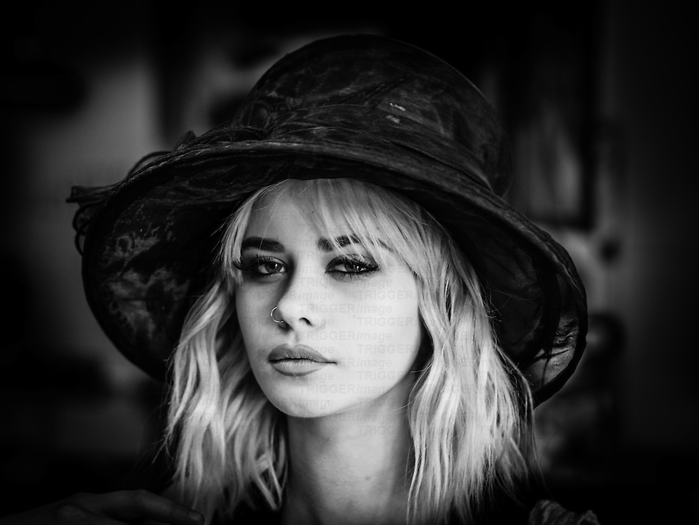 Vignetted shot of blonde female model wearing a hat