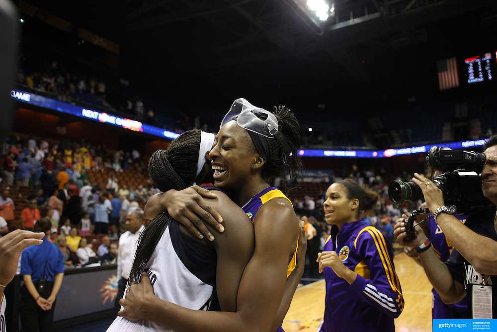 Sisters Chiney Ogwumike, (left), Connecticut Sun and Nneka Ogwumike, Los Angeles Sparks, (wearing face mask), hug at the end of the game after playing against each other for the fist time in the WNBA during the Connecticut Sun Vs Los Angeles Sparks WNBA regular season game at Mohegan Sun Arena, Uncasville, Connecticut, USA. 3rd July 2014. Photo Tim Clayton