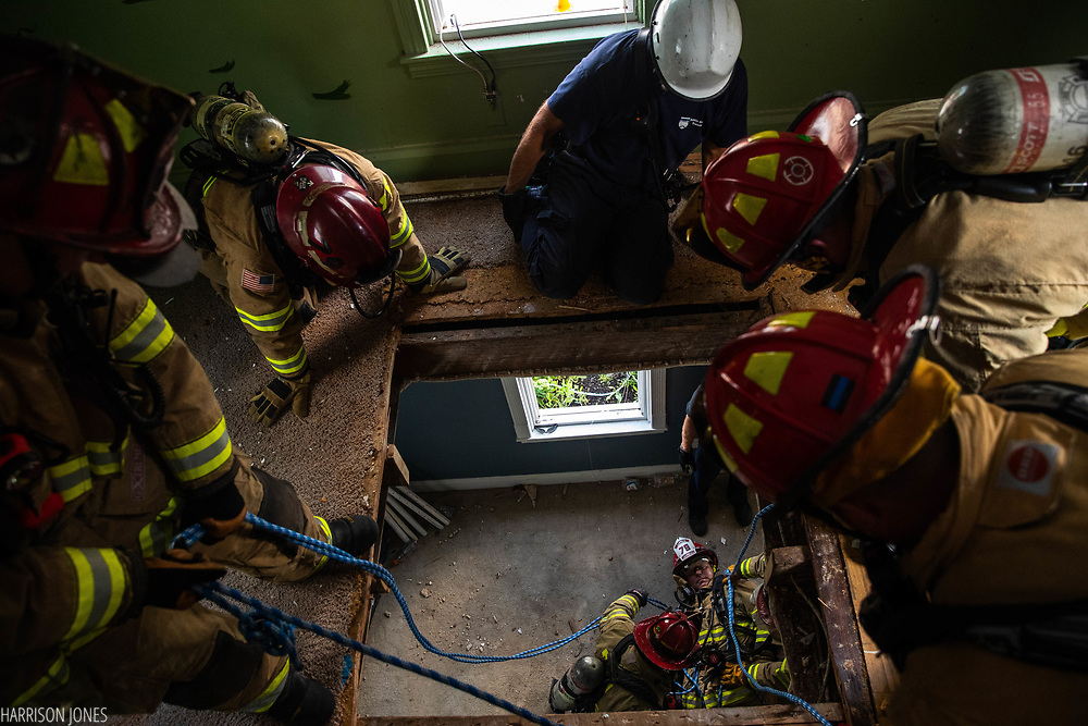 Firefighter Tim Tyler prepares a rope harness on Captain Chuck Amspacher, playing the role of a downed firefighter, as Hanover firefighters train on three acquired houses on the 300 block of Maple Ave., Saturday, Aug. 4, 2018, in Hanover. The vacant houses were donated by Ox Industries for emergency services to train on before they are demolished. Firefighters spent the day training on firefighter rescue scenarios and breaching.