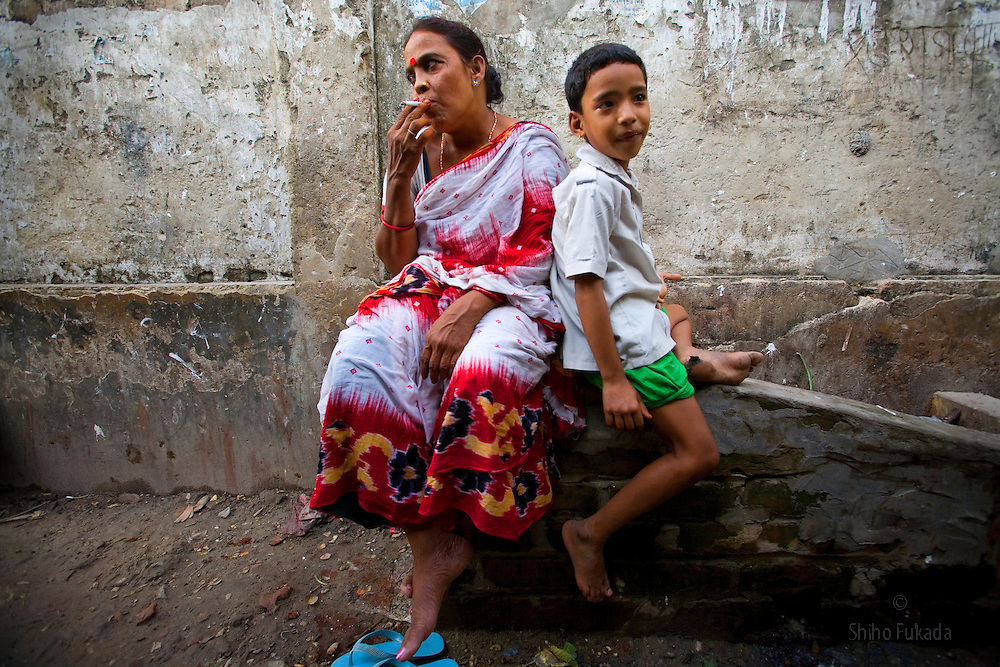 Aging sex worker Josna, 60, left, looks for a customer as her daughter Tanya, 7, sits by at brothel in Faridpur, Bangladesh.<br /> <br /> Deserted by the man who fathered her daughter, she, like many her age, has a difficult time pulling in enough clients to support her family. <br /> Growing old does not mean the end of one&rsquo;s career, but it does mean working harder for a fraction of the pay a younger woman can expect. When Josna can&rsquo;t buy food for Tanya, 7, she has to borrow from the neighbours.