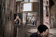 Egypt, Cairo:A young boy sits beside  pictures depicting Pope Shenouda, the head of the Coptic Church who died at age 88 in march 2012. ph.Christian Minelli.