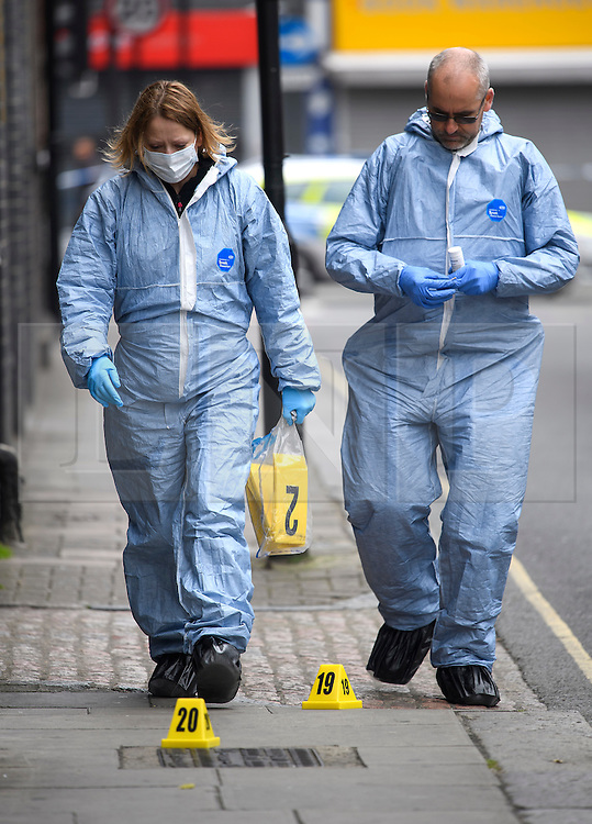 © Licensed to London News Pictures. 29/05/2016. London, UK.  Police forensics place evidence markers at the scene where a man in his 30's was stabbed in the early hours of the morning in Camden High Street. Police were called at 03:46hrs on Sunday, 29 May to Camden High Street close to Greenland Road following reports of a man suffering a stab wound. Officers and the London Ambulance Service attended. The man, believed to be aged in his late 30s, was taken to a central London hospital where he died at 04:37hrs. Photo credit: Ben Cawthra/LNP