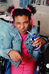 Young woman with Cerebral Palsy drinking beer from can in residential care centre,
