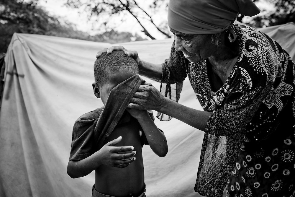 A woman washes the face of her grandson in a camp for those displaced by the recent earthquake in Petionville, outside Port-au-Prince, Haiti.