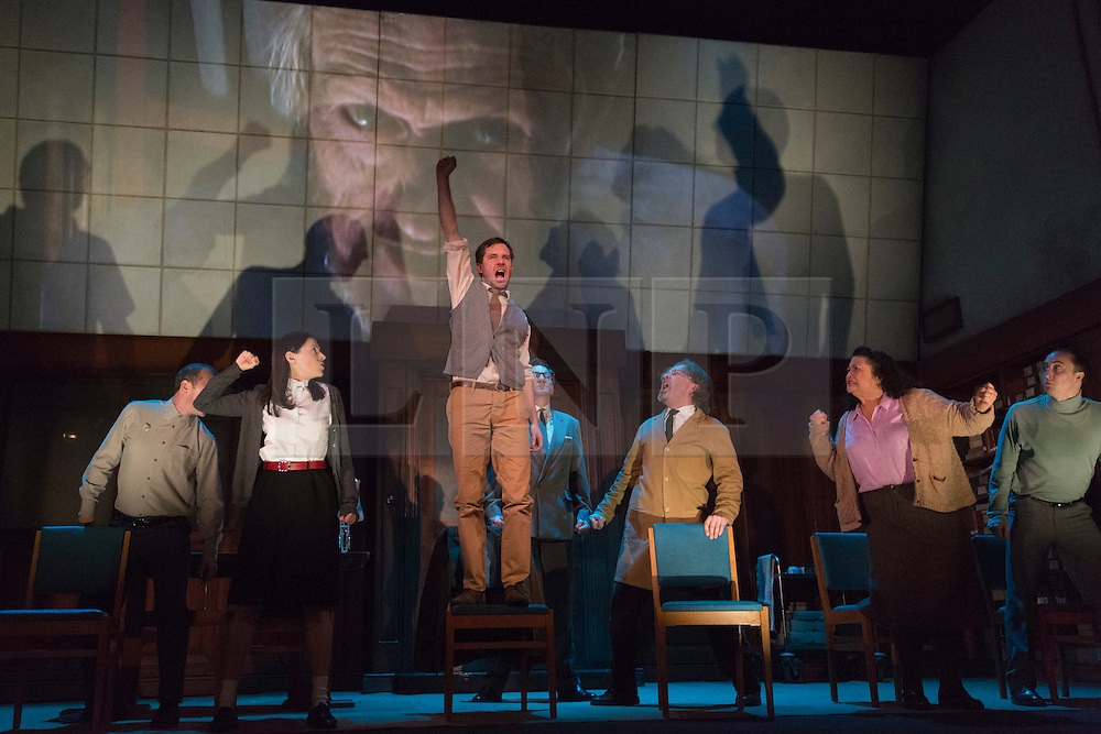 "© Licensed to London News Pictures. 08/05/2014. London, England. Pictured: L-R: Christopher Patrick Nolan as Martin, Hara Yannas as Julia, Sam Crane as Winston, Tim Dutton as O'Brien, Stephen Fewell as Charrington, Mandi Symonds as Mrs Parsons and Matthew Spencer as Syme during the Two Minutes Hate.The Play ""1984"" by George Orwell transfers to the Playhouse Theatre until 19 July 2014. A new adaptation for the stage by Robert Icke and Duncan MacMillan. With Sam Crane as Winston Smith. Photo credit: Bettina Strenske/LNP"