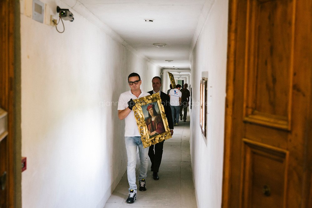 FLORENCE, ITALY - 3 JUNE 2018: Museum technicians transport two Raphael paintings, &quot;Portrait of a Young Man with an Apple&quot; and &quot;Portrait of Pope Julius II&quot;   through the  Vasari corridor, an<br /> 800-meter long passageway which links Palazzo Pitti to the Uffizi gallery, here to Palazzo Pitti, in Florence, Italy, on June 3rd 2018. The Vasari corridor is used to move paintings between the Uffizi gallery and Palazzo Pitti.<br /> <br /> As of Monday June 4th 2018, Room 41 or the &ldquo;Raphael and Michelangelo room&rdquo; of the Uffizi is part of the rearrangement of the museum's collection that has<br /> been defining Uffizi Director Eike Schmidt&rsquo;s grander vision for the Florentine museum.<br /> Next month, the museum&rsquo;s Leonardo three paintings will be installed in a<br /> nearby room. Together, these artists capture &ldquo;a magic moment in the<br /> first decade of the 16th century when Florence was the cultural and<br /> artistic center of the world,&rdquo; Mr. Schmidt said. Room 41 hosts, among other paintings, the dual portraits of Agnolo Doni and his wife Maddalena Strozzi painted by Raphael round 1504-1505, and the &ldquo;Holy Family&rdquo;, that Michelangelo painted for the Doni couple a year later, known as the<br /> Doni Tondo.