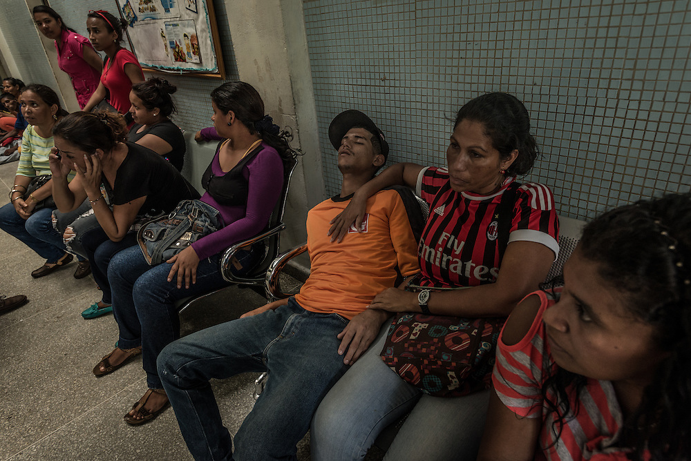 "SAN FELIX, VENEZUELA - MAY 24, 2016: Maribel Supero (second from left) clutched her son, Daniel Guzmán, 23, (center in orange shirt) as he trembled, so sick that he was unable to walk or even speak. Mr. Guzmán works as an illegal gold miner, and had been sick with malaria for 21 days when this photo was taken. His mother had taken him to several hospitals in search of medicine but had not found any yet. They had been waiting in the clinic lobby since the day before, waiting for malaria medicine to be delivered. Mr.  Guzmán was one of hundreds of people overflowing the small clinic, all with symptoms of malaria: fevers, icy chills and uncontrollable tremors. A handful of doctors and hospital staff tried their best to test each patient for malaria: pricking their ears for a blood sample in a room without air conditioning and no lights because the government had cut power to save electricity. There were no medicines to be distributed, because the health ministry had not delivered any this day. Frustrated patients protested in the street outside of the hospital pleading for malaria medicine to be delivered.  Dr. Griselda Bello waved her hands helplessly to tell yet another patient that there was no medicine that day. ""Come back tomorrow at 10 a.m.,"" she said. ""My God,"" the patient said. ""Someone might die by then."" ""Indeed they might,"" she said. The spread of malaria in Venezuela is a state secret. Since 2007, the government has not submitted annual epidemiological reports on the disease and says there is no epidemic. But the most recent report, obtained by The New York Times from Venezuelan doctors involved in compiling it, confirms a surge is underway.  Last year, malaria cases rose 56% to 136,000 cases, the highest level in 75 years when the state began efforts to eradicate the disease, according to the report. Malaria has cut a wide swath through the country with cases now present in half of its 23 states. And among the strains present here is Plasmodim falcipa"