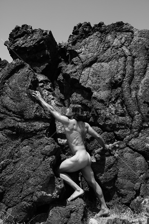 nude man and volcanic rock formation