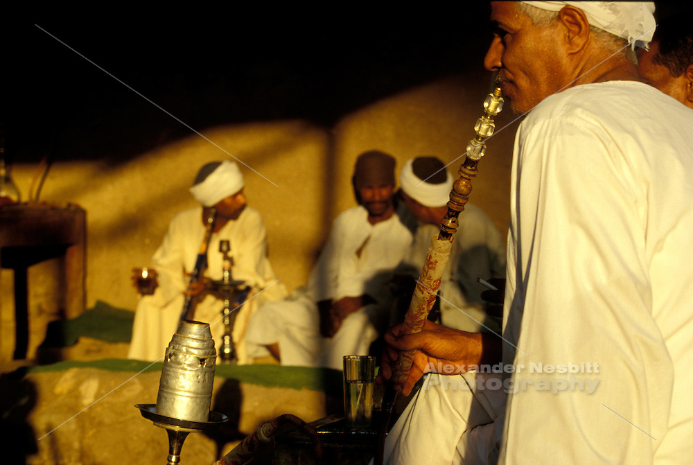 Men smoke water pipes (Sheesha) in a traditional cafe, west bank, Luxor, Egypt.