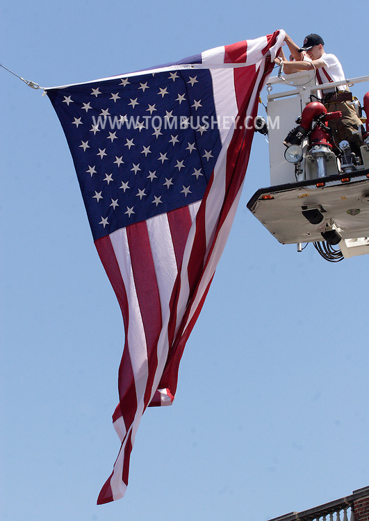 Middletown, NY - Bill Kautz Jr. and his father Capt. Bill Kautz remove a large American flag that was hanging between two ladder trucks during funeral services for Donald H. Kimble Jr., a former chief of the Middletown Fire Department, on Aug. 11, 2007..