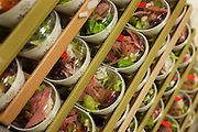 "Meat salads are stacked in readiness for an airline flight in the world's largest independent provider of airline catering and provisioning services, Gate Gourmet, on the southern perimeter road at Heathrow Airport, West London. Gate Gourmet serve more than 200 million meals on 2 million airline flights a year to their 250-plus airline customers at more than 100 airport locations around the globe. Apart from creating the bespoke meals for an airline's culture and ethnic demands, that pack the pre-flight carts, deliver and load into the aircraft galleys and afterwards, they dispose of the waste and strip, wash and sterilize the equipment. From writer Alain de Botton's book project ""A Week at the Airport: A Heathrow Diary"" (2009). ."
