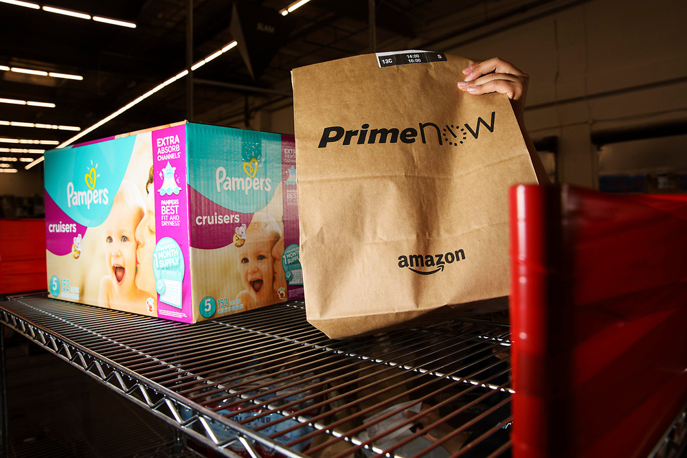 An Amazon associate grabs a bag next to Pampers diapers at the Amazon.com Inc. Prime Now fulfillment center warehouse on Monday, March 27, 2017 in Los Angeles, Calif. The warehouse can fulfill one and two hour delivery to customers. Complex supply chains such as Amazon's and e-commerce trends will impact city infrastructure and how things move through cities. © 2017 Patrick T. Fallon