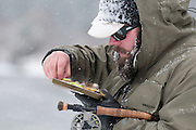 Tim Woodard searches his fly box for a steamer to hook a trout during a snowstorm on the South Fork of the Snake River, Idaho.