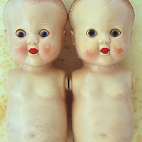 Faces and limbless bodies of two identical vintage baby dolls with big staring blue eyes and red lips and slightly scuffed and soiled