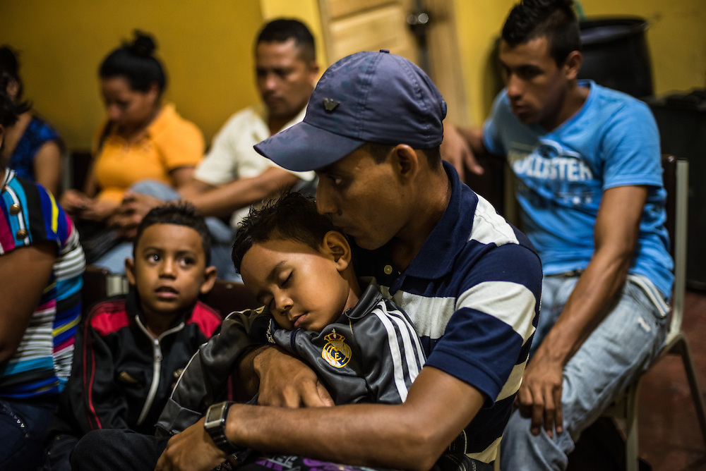 SAN PEDRO SULA, HONDURAS - MAY 25, 2014:  A man migrating north with two young children waits to catch a late-night bus from San Pedro Sula, Honduras to Guatemala City, Guatemala. While waiting, he read highlighted scripture from a small red Bible, and told a reporter that he believes God will protect him during the hard journy north.  The manager of the bus line estimated over 80 percent of this route's passengers are migrants trying to enter the United States illegally. PHOTO: Meridith Kohut for The New York Times