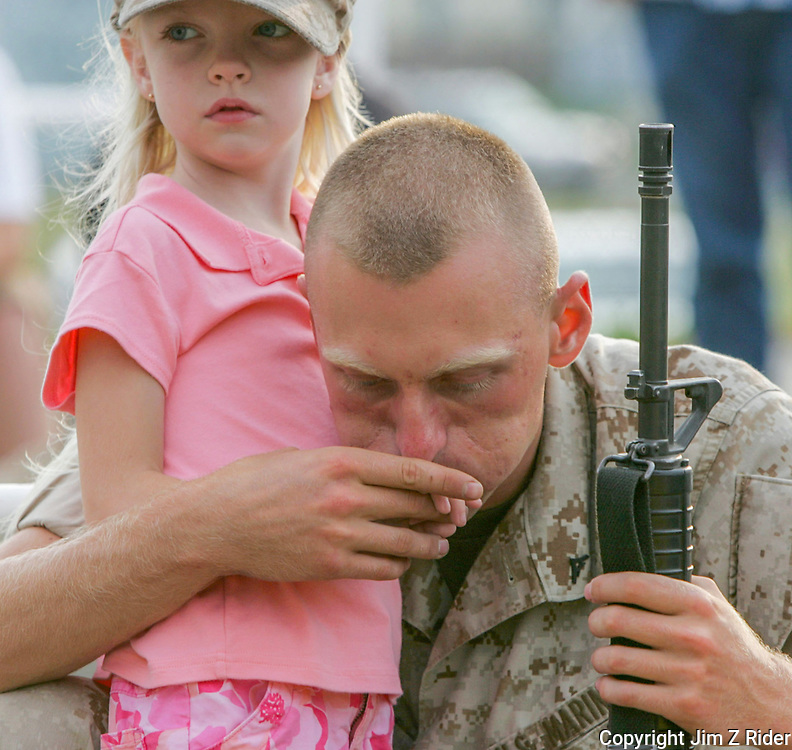 LCPL Steve Spitz, 22, of Anderson, Indiana, kisses the hand of his sister, Doria Phelps, 5, as he prepares to deploy to Iraq from the Army National Guard and Marine Reserve Center in South Bend, Indiana.  LCPL Spitz belongs to the 6th Engineering Support Battalion.