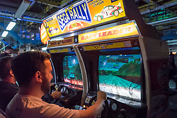© Licensed to London News Pictures. 12/08/2018. LONDON, UK. Men play Sega Rally, a nineties driving game, at Play Expo London, a video games show featuring consoles, handhelds, computers, vintage arcades and pinball machines, organised by Replay Events taking place at the Printworks in Canada Water, East London.  Photo credit: Stephen Chung/LNP