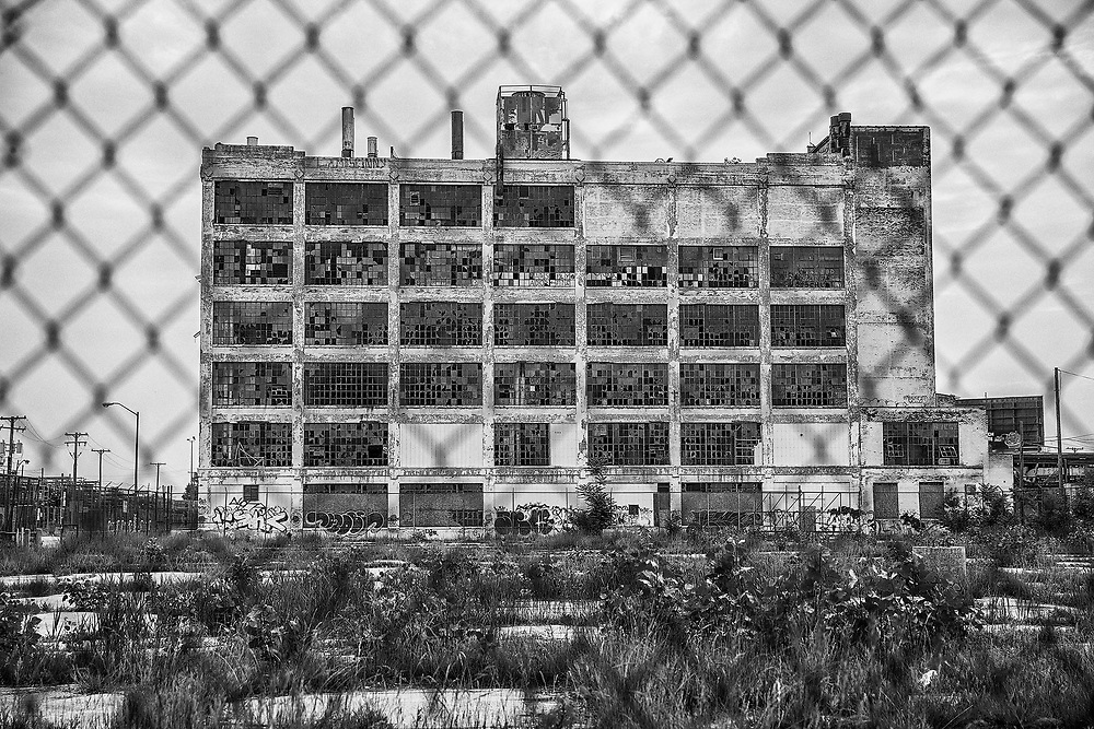 DETROIT, USA - JUNE 12, 2015: The Fisher Body Works factory in Detroit was in use and producing automobiles from 1919 to 1984. After the plant was closed, windows were broken, weeds filled the parking lot, and the outside walls were gradualy covered in graffitti.