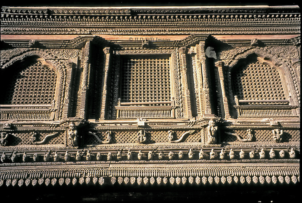 Detail of carved wooden ornamented windows and screens in Newari style on the exterior of the royal palace, Kathmandu, Durbar Square.