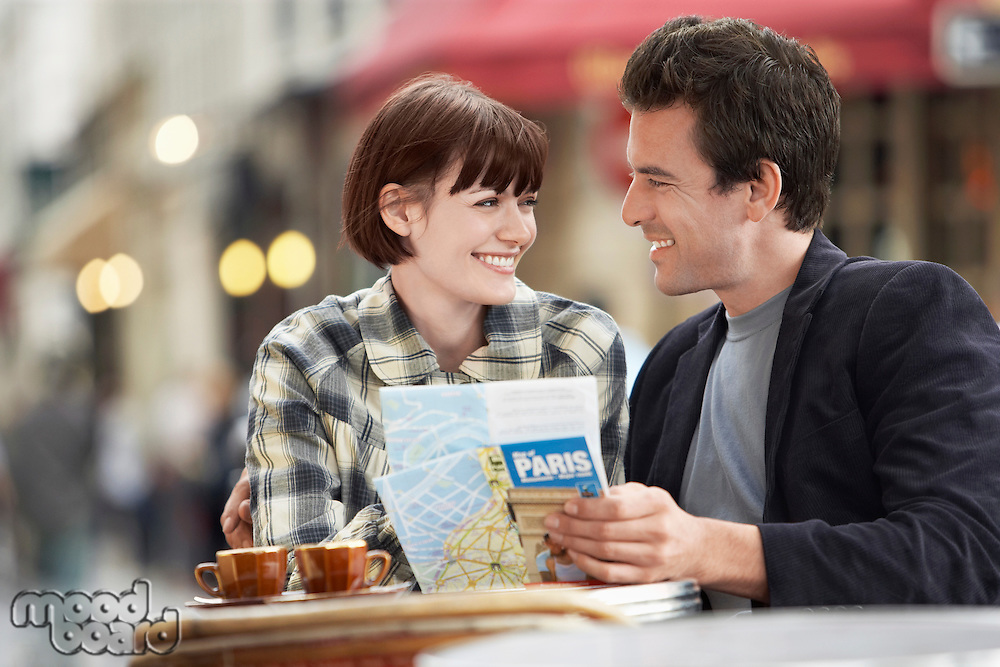 France Paris Couple reading map sitting outside cafe