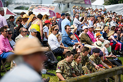 © London News Pictures. 12/05/2016. Windsor, UK. People sit in the sunshine as they watch the first day of the 2016 Royal Windsor Horse Show, held in the grounds of Windsor Castle in Berkshire, England. The opening day of the event was cancelled due to heavy rain and waterlogged grounds. This years event is part of HRH Queen Elizabeth II's 90th birthday celebrations.  Photo credit: Ben Cawthra/LNP
