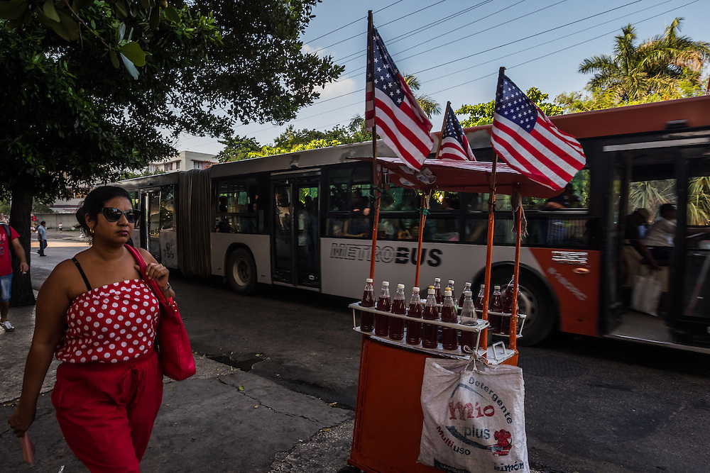 HAVANA, CUBA - JULY 20, 2015: A woman walks past a snowcone cart decorated with American flags in Havana. After more than half a century defined by mistrust and rancor, the United States officially reopened its six-story embassy in Havana today, marking a watershed moment of transition for the two countries as they lean toward closer diplomatic ties and ease past one of the last remnants of the Cold War.  President Barack Obama, when announcing an end to the diplomatic freeze, eased travel restrictions, opened the door for more remittances to Cuba and expanded the amount of goods that visiting Americans could bring back home – like Cuban cigars and rum. He even removed the country from the list of nations that sponsor terrorism. President Raul Castro, meanwhile, has spent the last five years, before the thaw even began with the Obama administration, attempting to alter his nation's economic dysfunction, ordering the firing of government employees, encouraging a slow but fresh influx of Cubans into self-employment and even creating a special economic zone in the coastal city of Mariel to attract foreign investment.  PHOTO: Meridith Kohut for The New York Times