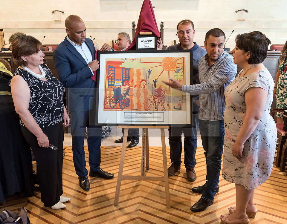 © Licensed to London News Pictures.  29/06/2018; Bristol, UK. Memorial event at Bristol City Hall, honouring Kamil Ahmad and Bijan Ebrahimi: Exploring Disability and Migration. Picture of family members examining a mural in memory of Kamil Ahmad; left to right: Mojgan (sister of Bijan), Bristol Mayor Marvin Rees, Dilen (cousin of Kamil), Kamran (brother of Kamil), Manizhah (sister of Bijan). Kamil Ahmad and Bijan Ebrahimi were both disabled men who came to the UK seeking sanctuary. Both were brutally murdered in Bristol. Kamil Ahmad was a disabled Kurdish man who came to Britain seeking sanctuary after having been imprisoned and tortured in Iraq. He was murdered in his supported accommodation in Bristol on 7th July 2016. Bijan Ebrahimi was a disable Iranian refugee, living in Bristol, who was murdered at his home on 14 July 2013. Two men, police beat manager PC Kevin Duffy, and police community support officer Andrew Passmore, were both jailed over how they dealt with Ebrahimi after being found guilty of misconduct in a public office. They and two other constables, Leanne Winter, 38, and Helen Harris, 40, who arrested Ebrahimi, have been dismissed from the force. Bristol Mayor Marvin Rees said sorry to the families of both men at the memorial event at Bristol City Hall, part of Bristol Refugee Festival, where a mural in memory of Kamil Ahmad was unveiled. Afterwards a march in support of disabled refugees was held in the centre of Bristol. <br /> Photo credit: Simon Chapman/LNP