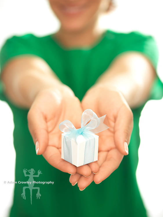 Close up of a small, white gift box  wrapped with light blue ribbon, held by a woman (20-30).